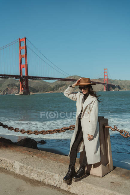 Side view of smiling young lady in trendy outfit with hat and sunglasses standing on embankment against Golden Gate Bridge in California in sunny day — Stock Photo