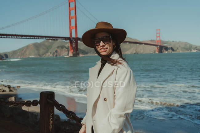 Side view of smiling young woman in trendy outfit with hat and sunglasses standing on embankment against Golden Gate Bridge in California in sunny day — Stock Photo