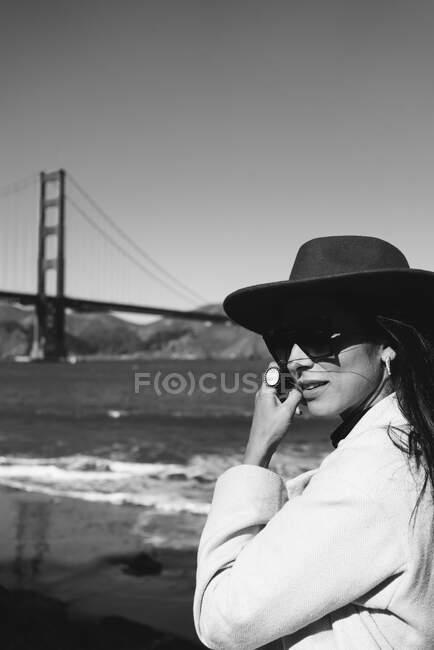 На стіні вимальовується усміхнена молода леді в модному одязі з капелюхом і сонцезахисними окулярами, що стоять на набережній проти моста Золоті Ворота в Каліфорнії в сонячний день. — стокове фото