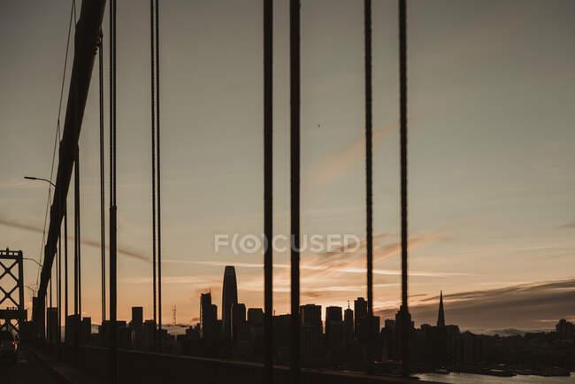 Vista da ponte da baía de São Francisco e da cidade em tempo calmo da manhã durante o nascer do sol com céu nublado no fundo — Fotografia de Stock