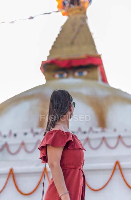 Vista laterale della donna in piedi vicino al tempio buddista con ghirlande decorative e torre sotto il cielo nuvoloso alla luce del giorno — Foto stock