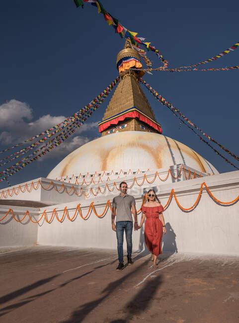 Casal de mãos dadas e olhando para a câmera enquanto está perto do templo budista com guirlandas decorativas e torre sob céu nublado à luz do dia — Fotografia de Stock