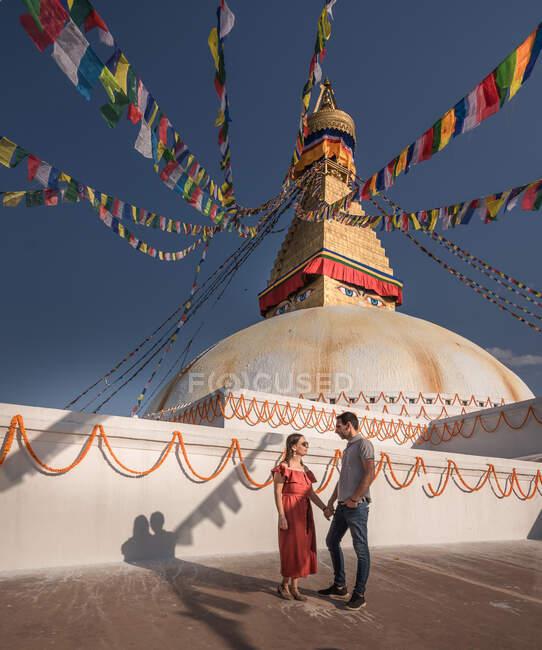 Пара держась за руки и глядя друг на друга, стоя рядом с буддийским храмом с декоративными гирляндами и башней под облачным небом при дневном свете — стоковое фото