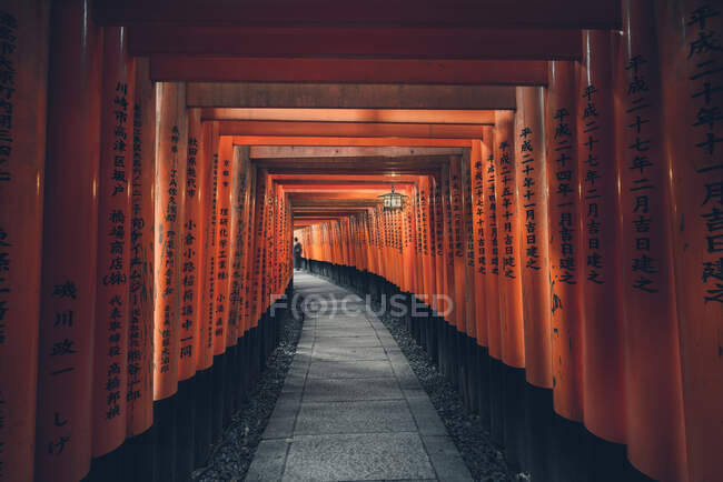 Fushimi Inari Taisha with stone pathway surrounded by red Torii gates and illuminated by traditional lantern with distant unrecognizable person — Stock Photo