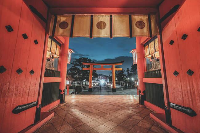 Angle bas de sanctuaire religieux avec portes torii et murs en bois rouge à Kyoto dans la soirée — Photo de stock