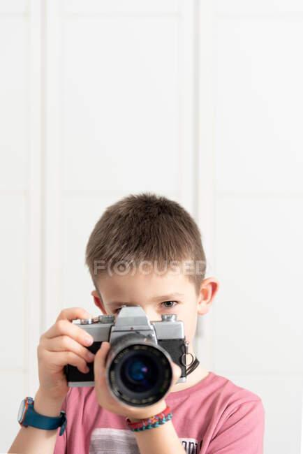 Bambino carino in abbigliamento casual scattare foto su fotocamera retrò mentre in piedi in appartamento moderno e divertente durante il fine settimana — Foto stock