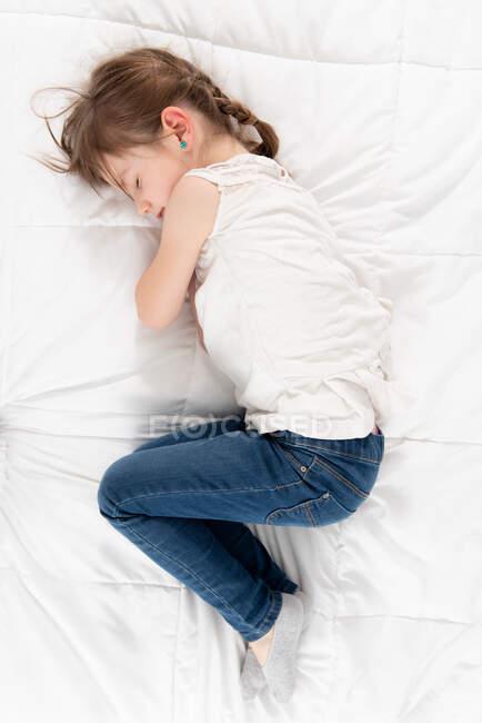 De cima vista lateral da criança adorável em roupas casuais deitado em cama macia em apartamento e descansando com os olhos fechados durante o fim de semana em casa — Fotografia de Stock