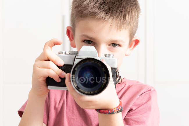 Cute child in casual wear taking photo on retro camera while standing in modern apartment and entertaining during weekend — Stock Photo