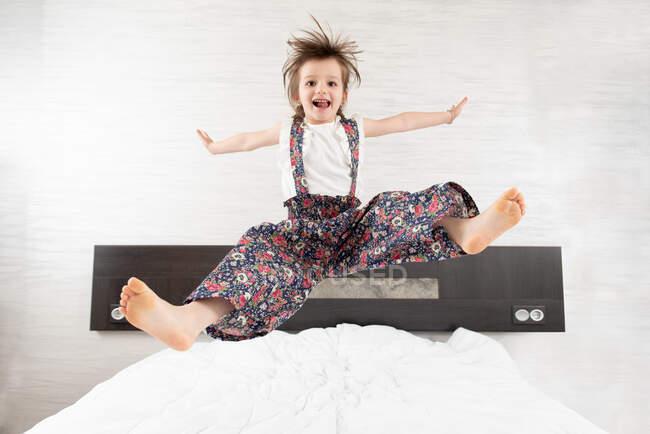 Conteúdo criança em macacão no momento de pular na cama com os braços estendidos e pernas olhando para a câmera — Fotografia de Stock