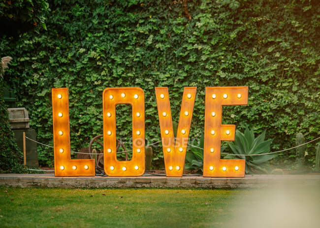 Installation of wooden glowing letters placed in courtyard near green hedge for wedding celebration — Stock Photo