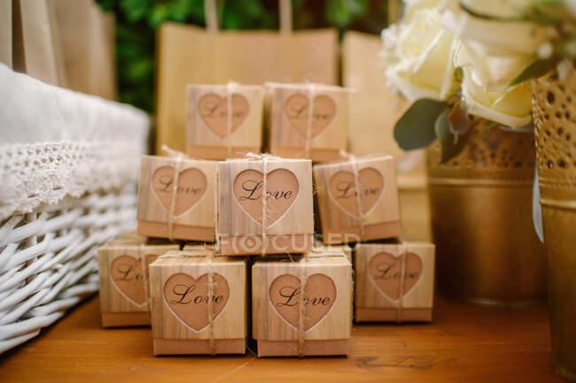 Pile de cadeaux dans des boîtes en papier placées sur une table en bois le jour du mariage — Photo de stock