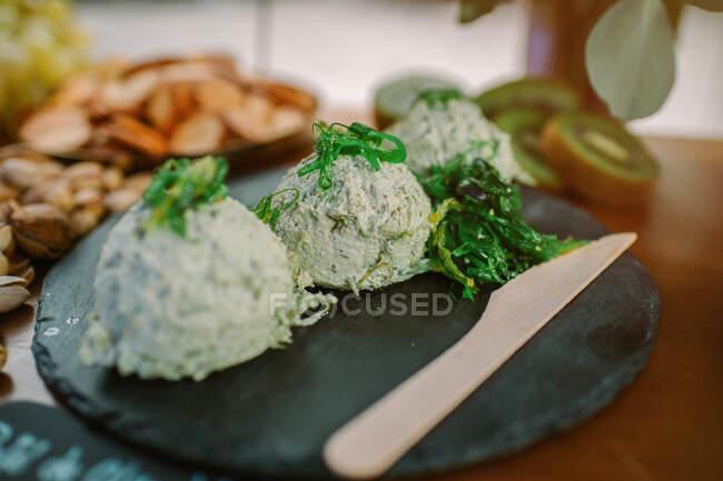 Plato sabroso hecho de requesón adornado con algas verdes y colocado en pizarra - foto de stock