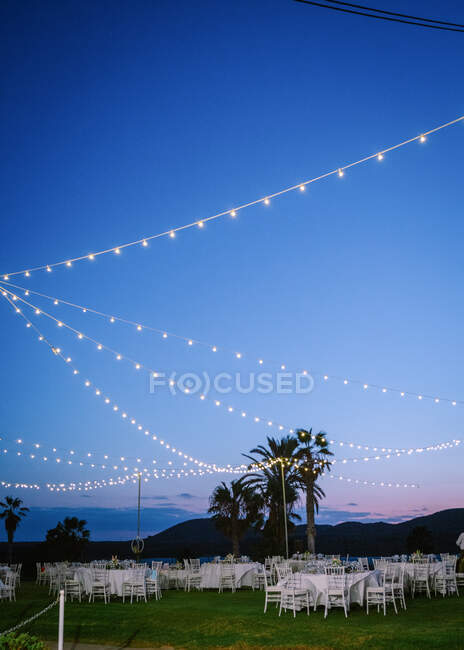 Glowing garlands hanging over banquet tables and chairs prepared for wedding party in evening — Stock Photo