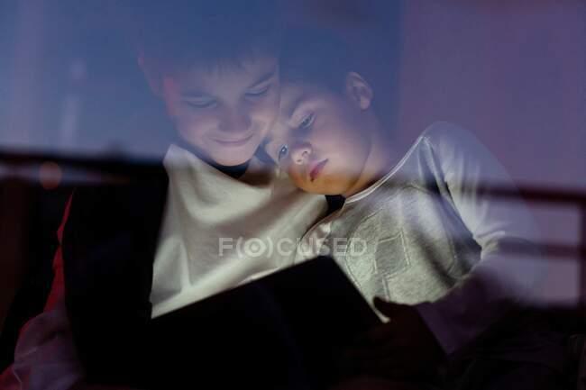 Baixo ângulo de adoráveis meninos em casual desgaste abraçando e assistindo vídeo interessante à noite, enquanto passa o fim de semana em casa — Fotografia de Stock