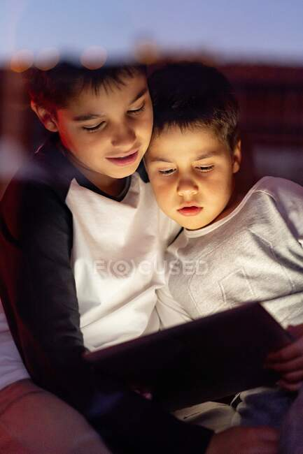 Cute brothers watching cartoon on tablet together — Stock Photo