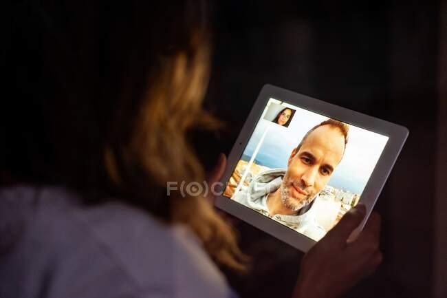 Visão traseira da namorada sentada no quarto escuro com tablet e falando em videochamada com namorado enquanto usa tablet — Fotografia de Stock