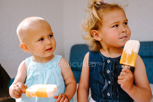 Cute little girls eating yummy popsicles while enjoying summer and sitting together in backyard — Stock Photo