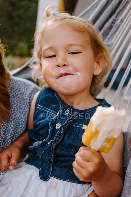 Contenido niño comiendo paleta casera mientras se relaja en la terraza en verano - foto de stock
