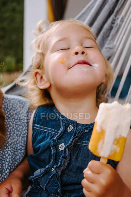 Contenuto bambino che mangia ghiacciolo fatto in casa su bastone mentre si rilassa sulla terrazza in estate — Foto stock