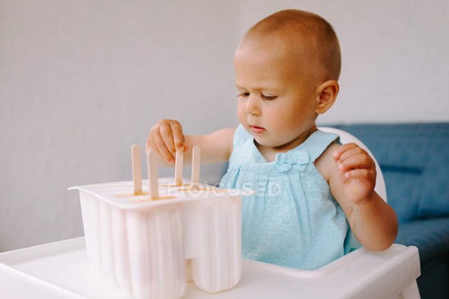 High angle of cute toddler sitting on high chair on terrace and eating delicious popsicles — Stock Photo