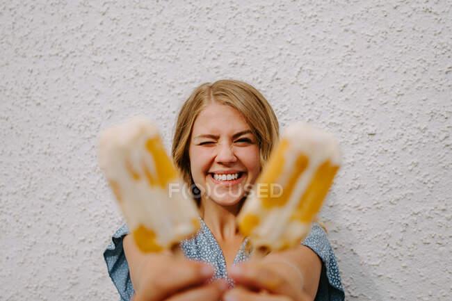 Женщина моргает глазами и делает смешные гримасы с вкусными ледяными леденцами на палочках на белом фоне — стоковое фото