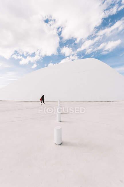 Неузнаваемый человек идет по пустой площади рядом с белым изогнутым зданием Международного культурного центра Оскара Нимейера, расположенного в Астурии в Испании в солнечные дни на фоне синего облачного неба — стоковое фото