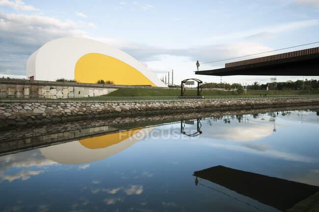 Зовні вигнутого бетонного залу будівлі Міжнародного культурного центру імені Оскара Німеєра, який видно з берегу річки і відбитий у воді в Астурії (Іспанія). — стокове фото