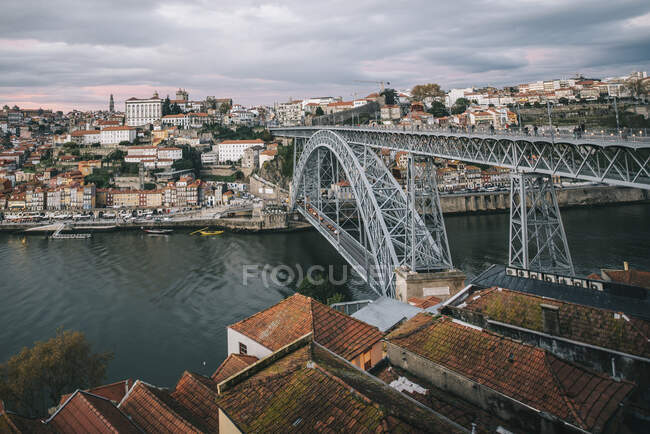 Drone vista di stupefacente paesaggio urbano con ponte sul fiume calmo e case residenziali sotto il tramonto cielo nuvoloso — Foto stock