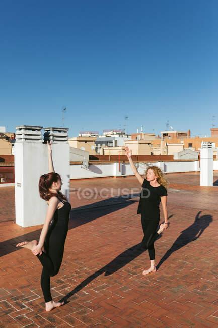 Жінки разом практикують йогу на даху. — стокове фото