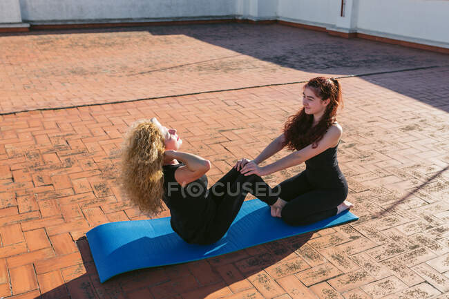 Vista lateral de ángulo alto de mujer madura con hija joven haciendo asana sentada mientras practican yoga en pareja juntos en la terraza soleada en la azotea - foto de stock