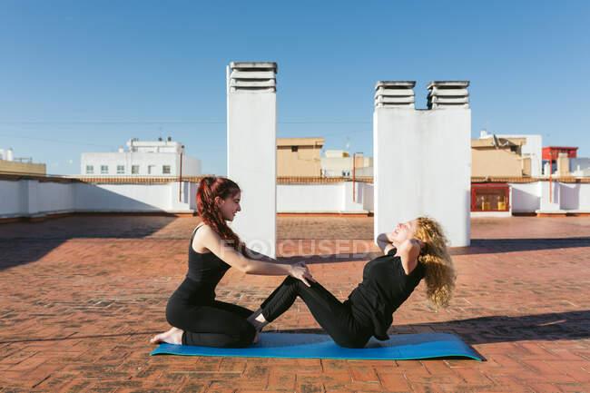 Mujeres practicando yoga en pareja en la azotea - foto de stock