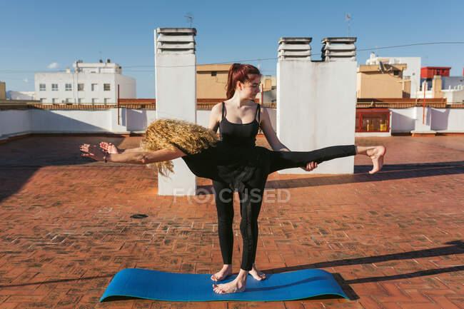 Cuerpo completo de hembra irreconocible realizando pose Guerrera III con ayuda de pareja mientras practican yoga juntas en la terraza de la azotea de la ciudad - foto de stock