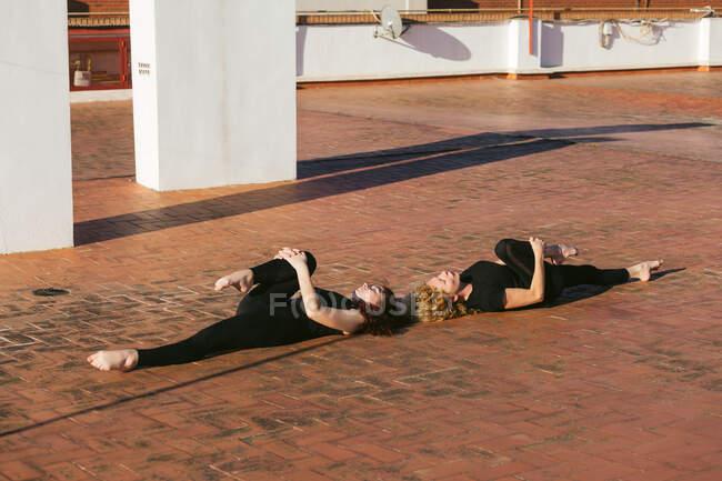 Полный вид сбоку тела тонких женщин в черной спортивной одежде лежащих в одной ноге ветра Удаление позы во время практики йоги на солнечной террасе на крыше — стоковое фото