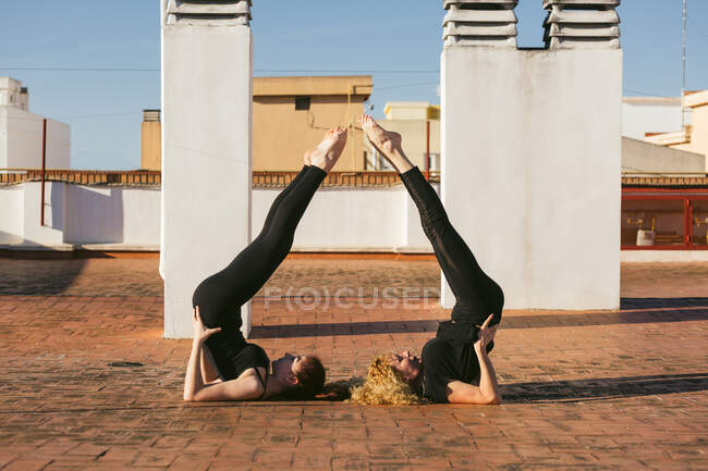 Side view of young female with mature mother doing Supported Shoulder Stand together while practicing partner yoga on rooftop of city building in sunny day — Stock Photo