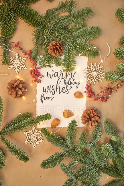 Chaleureux voeux de vacances lettrage sur carte entouré de décorations de Noël — Photo de stock