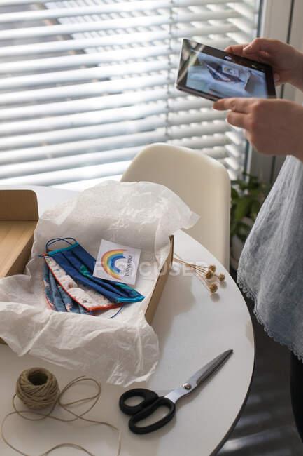 Обрезанный снимок женщины, фотографирующей маски ручной работы с благодарственной открыткой упакованной в коробку — стоковое фото