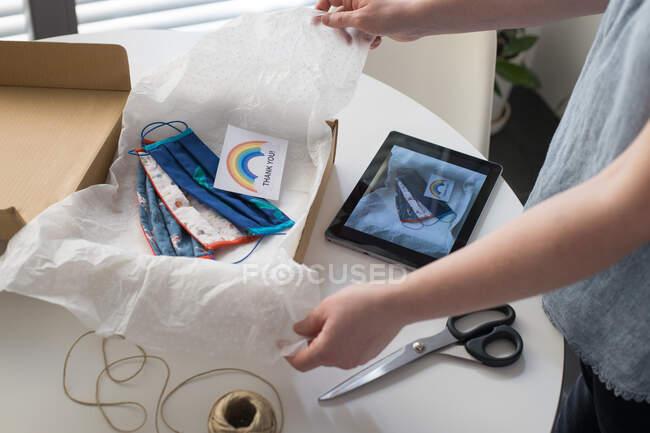 Обрезанный снимок женщины упаковки ручной работы маски в коробке с благодарственной открыткой — стоковое фото