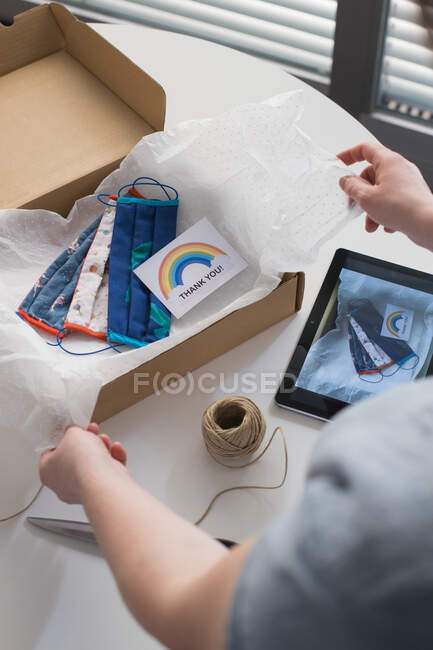 Cropped shot of woman packing handmade masks in box with thank you card — Stock Photo