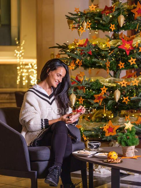Frau trinkt eine Tasse heiße Schokolade auf dem Sofa ihres Hauses mit Weihnachtsbaum und Weihnachtsdekoration im Hintergrund. — Stockfoto