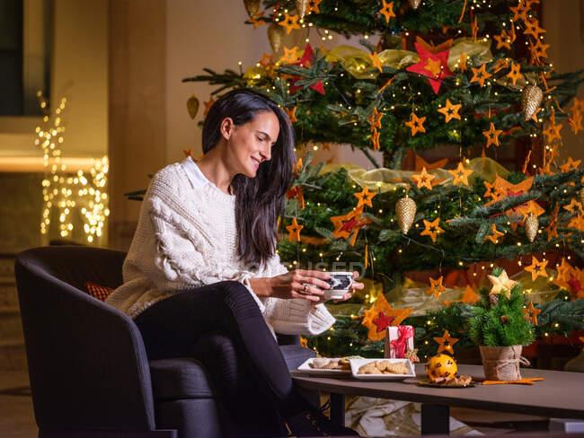 Donna che beve una tazza di cioccolata calda sul divano di casa sua con un albero di Natale e decorazioni natalizie sullo sfondo. — Foto stock