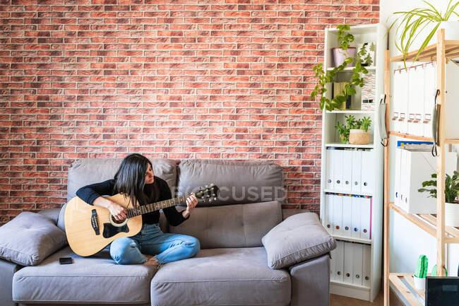 Femme jouant de la guitare assise sur son canapé à la maison et apprenant avec des leçons en ligne et certains masques sont suspendus en raison de confinement. Derrière il y a un mur de briques — Photo de stock