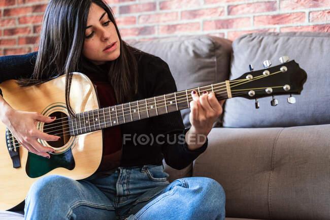 Eine Frau, die zu Hause auf ihrer Couch Gitarre spielt und mit Online-Unterricht lernt, und ein paar Masken hängen wegen der Eindämmung. Dahinter steht eine Mauer — Stockfoto