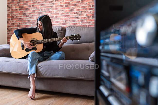 Mujer tocando la guitarra sentada en su sofá en casa y aprendiendo con lecciones en línea y algunas máscaras están colgando debido a la contención. Detrás de ella hay una pared de ladrillo - foto de stock