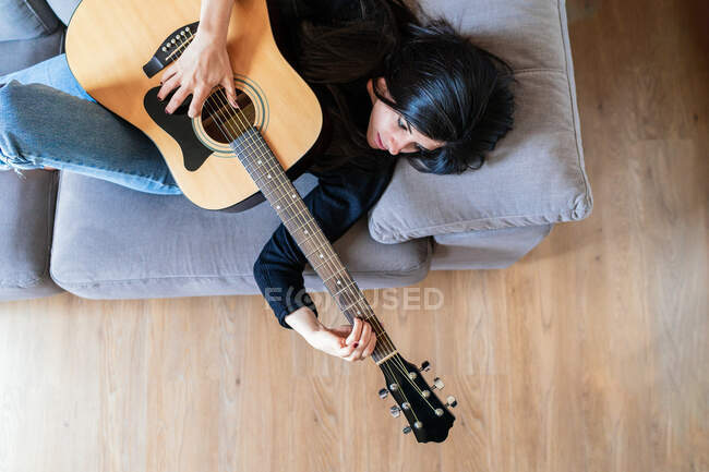 Woman playing guitar sitting on her couch at home and learning with online lessons and some masks are hanging due to containment. Behind it is a brick wall — Stock Photo