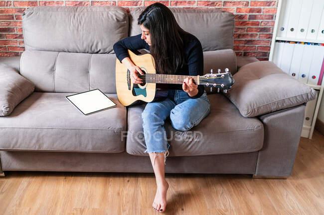 Frau, die zu Hause auf ihrer Couch Gitarre spielt und mit einem digitalen Tablet mit einem leeren Bildschirm von oben mit Online-Unterricht lernt — Stockfoto