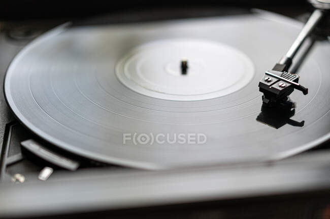 A black vinyl record is spinning on a vintage record player — Stock Photo