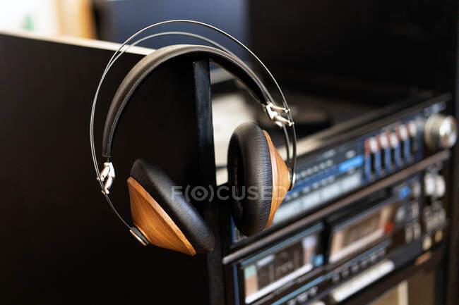 Vintage-Kopfhörer aus Holz befinden sich auf einer schwarzen Schallplatte im Plattenspieler — Stockfoto