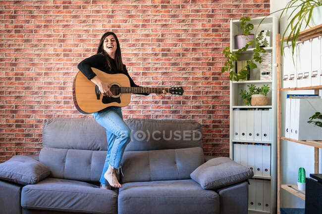 Woman smiling standing on a couch playing the guitar. Behind it is a brick wall — Stock Photo