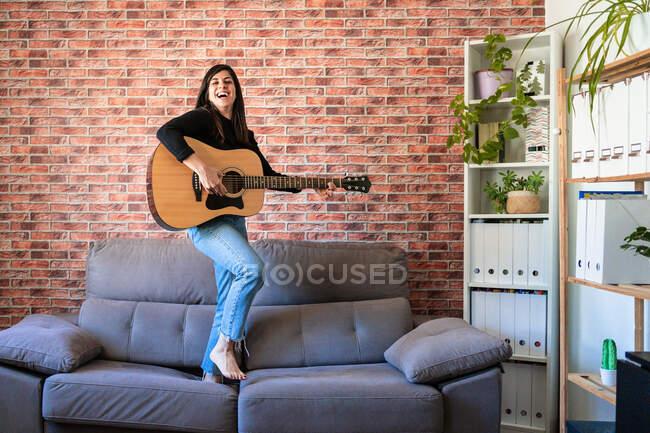 Femme souriante debout sur un canapé jouant de la guitare. Derrière il y a un mur de briques — Photo de stock