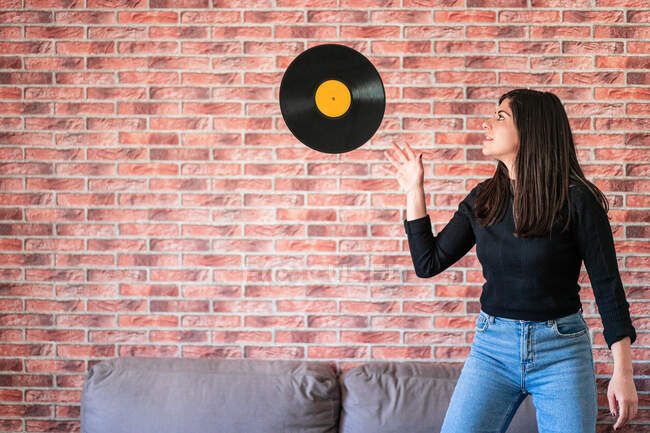 Anonymous young woman holding a black vinyl with her hands — Stock Photo